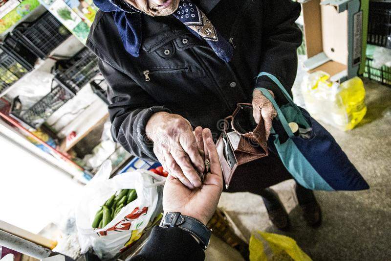 An elderly retired woman gives her the last money in a store. High iso and much noise for bigger drama stock images