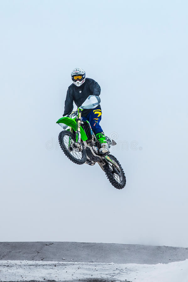 High jump athlete on a motorcycle. Miasskoe, Russia - January 16, 2016: high jump athlete on a motorcycle during Cup of Urals winter motocross royalty free stock photos