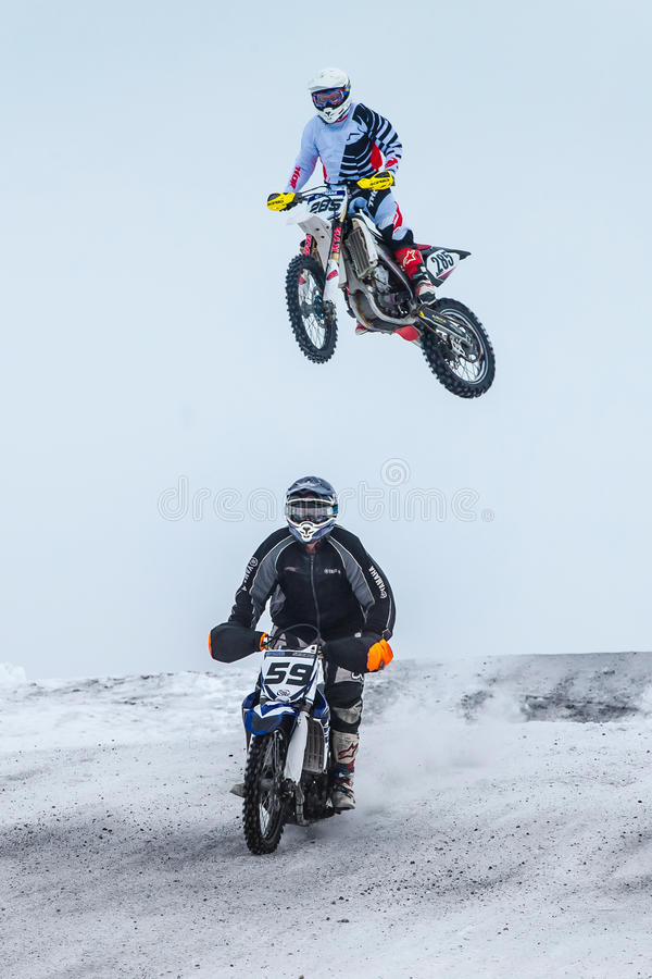 High jump and flight athlete motorcycle on a winter road. Miasskoe, Russia - January 16, 2016: high jump and flight athlete motorcycle on a winter road during royalty free stock photos