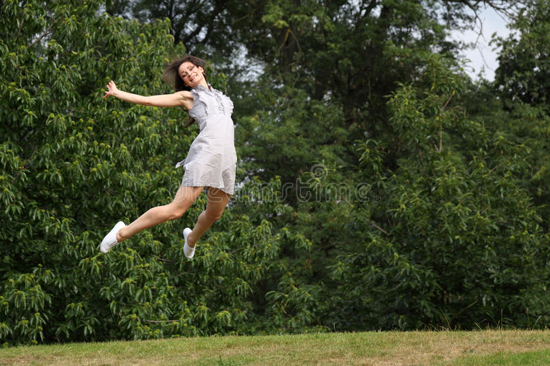 High jump in trees for success of beautiful girl royalty free stock photos