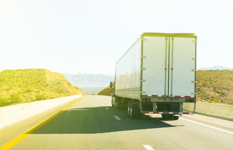 High key image of a haulage truck on a motorway. High key image of a white haulage truck on a motorway viewed from the rear on a sunny day stock image