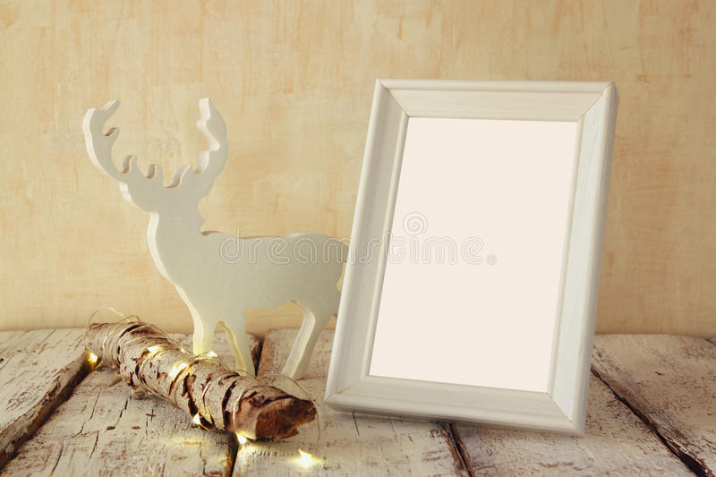 High key image of old tree log with fairy christmas lights, reindeer and blank photo frame on wooden table.selective focus royalty free stock photo