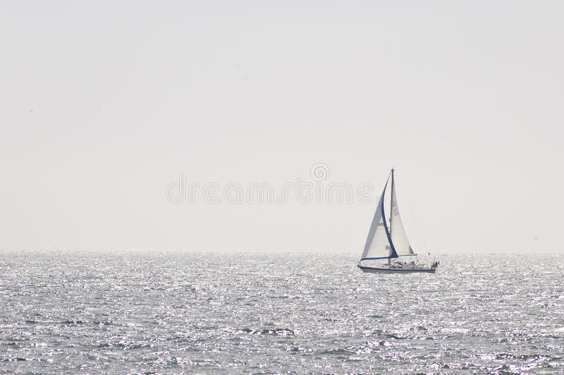 High Key Lone Yacht on the Horizon. A peaceful serene image depicting many things from adventure, sport, holiday vacations and recreation royalty free stock images