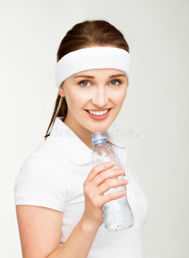 High key Portrait of attractive young woman drinking water isolated on white background. High key Portrait of attractive young woman drinking water smiling royalty free stock photo