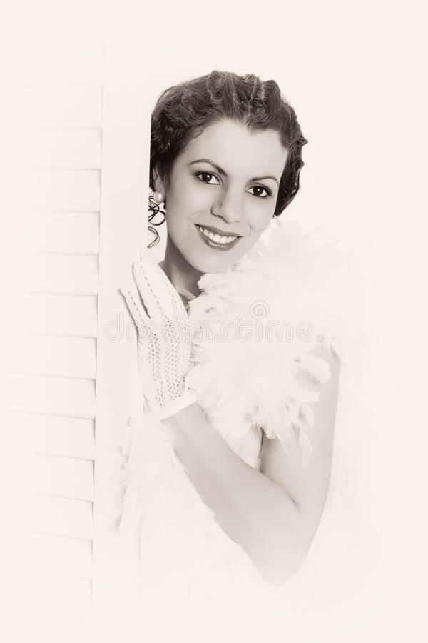 High key portrait 1920s woman. Young brunette in vintage 1920s feather boa looking from behind a folding screen in her boudoir stock photo