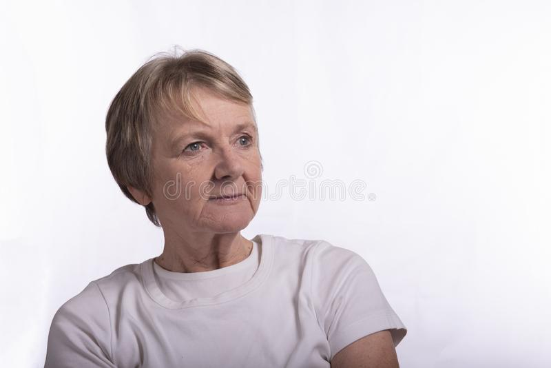 High key portrait of serious mature woman, taken with copy space. On a white background royalty free stock images