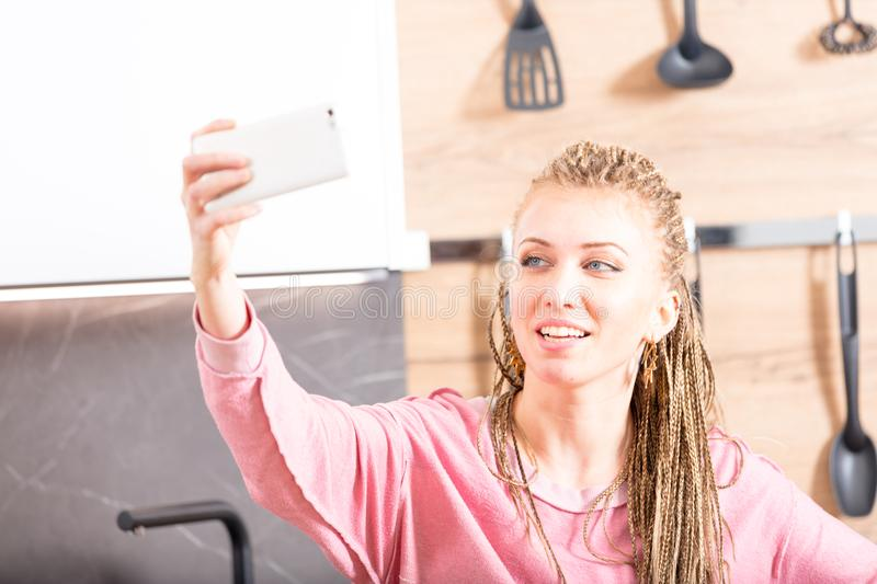 High key portrait of a woman taking a selfie. High key portrait of a trendy young woman with long braided blond hair taking a selfie on her mobile phone in a royalty free stock photography