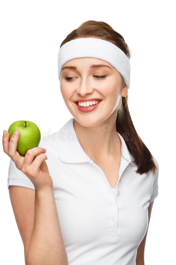 High key Portrait young woman holding green apple isolated on white background. High key Portrait of attractive healthy young woman holding green apple smiling royalty free stock image