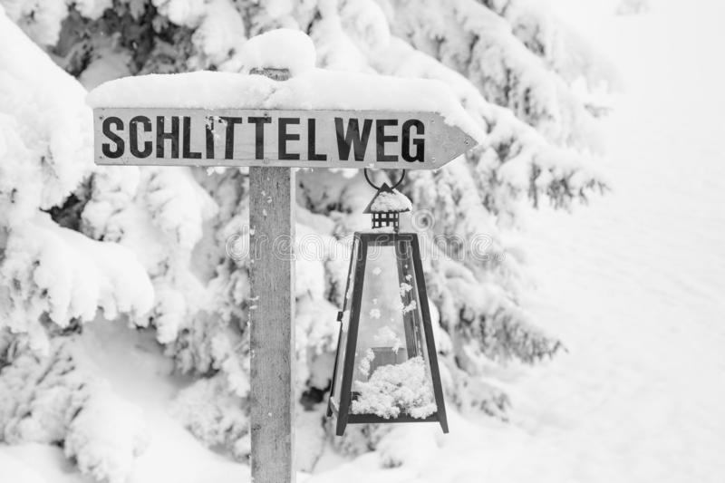 High-key winter landscape with a sign for the toboggan run. In the foothills of Switzerland royalty free stock photo