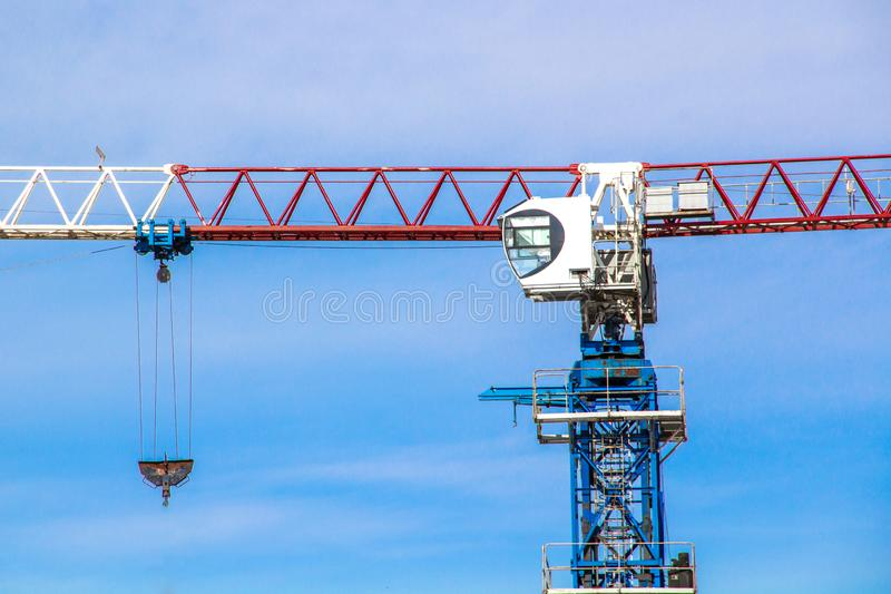 High lift construction crane with white, red and blue colors against a blue sky stock image