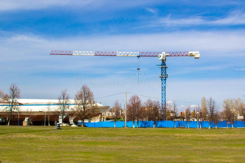 High lift construction crane with white, red and blue colors against a blue sky stock photos