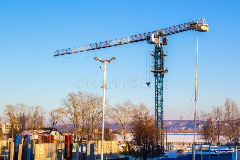 High lift construction crane with white, red and blue colors against a blue sky stock images