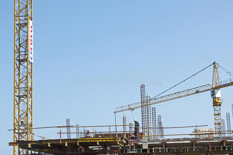 High lift Crane and Workers Woking on Construction Site royalty free stock photography