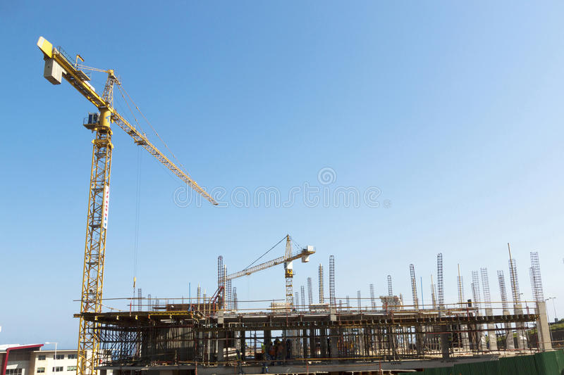High lift Crane and Workers Woking on Construction Site. MHLANGA RIDGE, DURBAN, SOUTH AFRICA - OCTOBER 21, 2016: High lift crane and many unknown people working stock photography