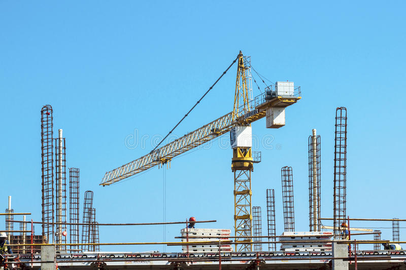 High lift Crane and Workers Woking on Construction Site. MHLANGA RIDGE, DURBAN, SOUTH AFRICA - OCTOBER 21, 2016: High lift crane and many unknown people working stock image