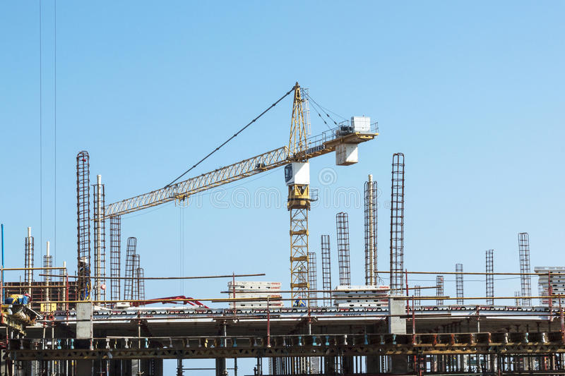 High lift Crane and Workers Woking on Construction Site. MHLANGA RIDGE, DURBAN, SOUTH AFRICA - OCTOBER 21, 2016: High lift crane and many unknown people working stock photos