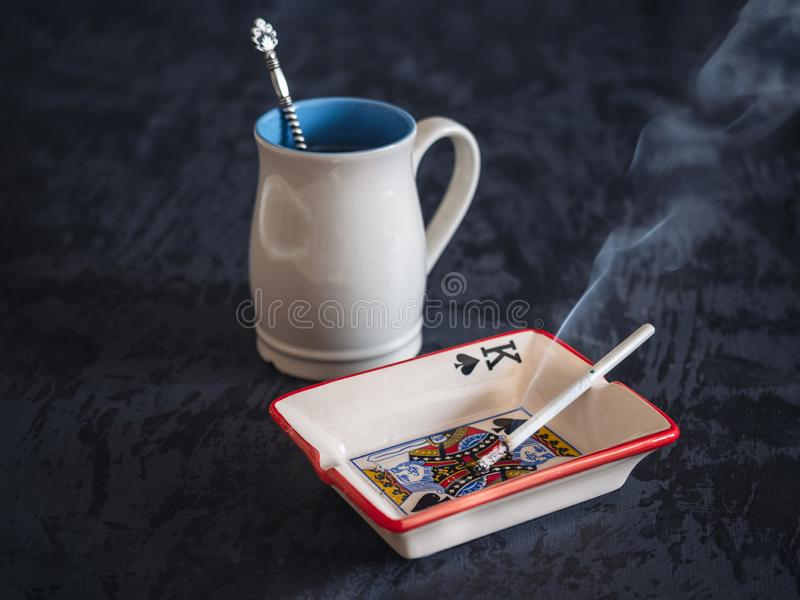A high light blue cup with hot tea, a lit cigarette in an ashtray, a bad smoking habit stock photos