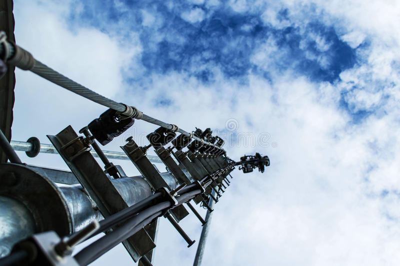 High mast metal structure telecommunication on tower with blue s. Ky royalty free stock images