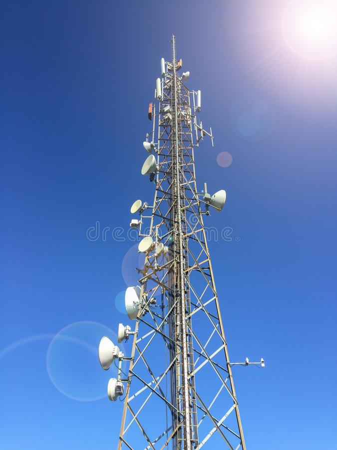 High metal radio cellular network antenna base station telecommunication tower with many microwave antennas. Transmitting and radiating high power radio waves royalty free stock photo