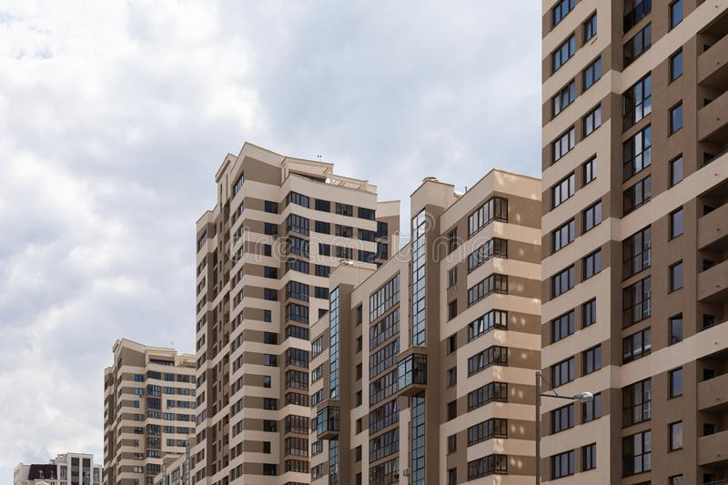 High modern luxury apartment in downtown, brown and beige tiled facade. Sky background, diagonal view, angle view. Ground view royalty free stock photo
