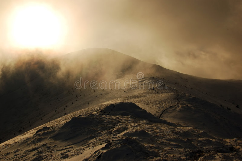 High mountain. Top of the high winter mountain and sun in the mist royalty free stock photos
