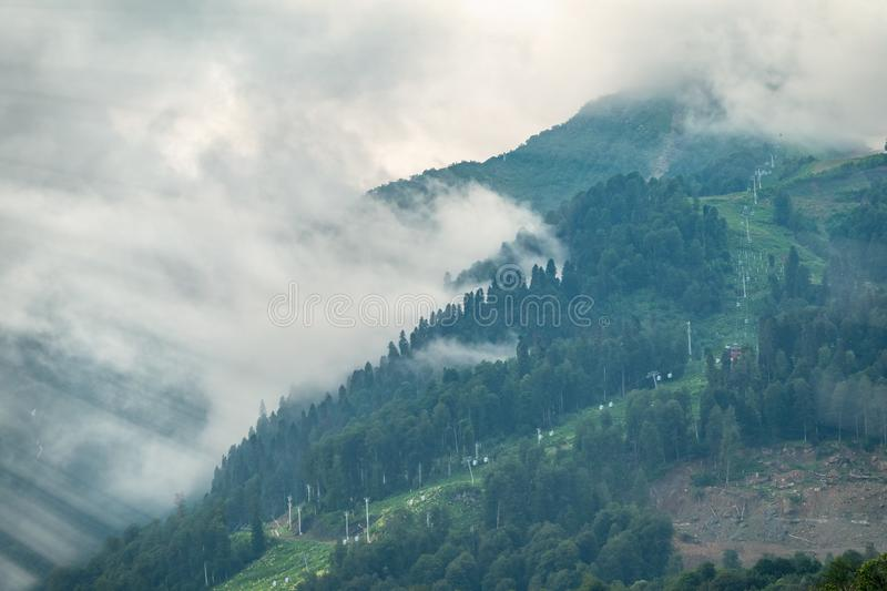 A high mountain with green slopes with a cable car disappeared into thick fog. The sun`s rays pass through the thick fog in the mountains stock images