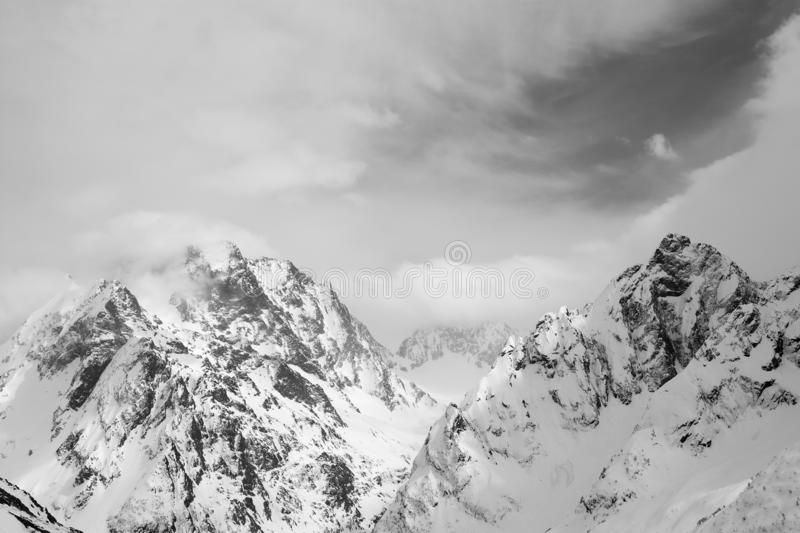 High mountain peaks covered with snow and sky with clouds. At winter day. Caucasus Mountains, region Dombay. Black and white toned landscape stock photo