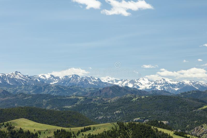 Western high rocky mountain range. High mountain peaks snow capped snowcapped Absaroka Beartooth mountains sunlight view Montana Wyoming USA grassy meadows royalty free stock images