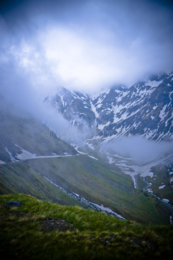 High mountain scenery. A beautiful vertical panoramic view of high mountain scenery with descending clouds and melting snow in the distance stock images
