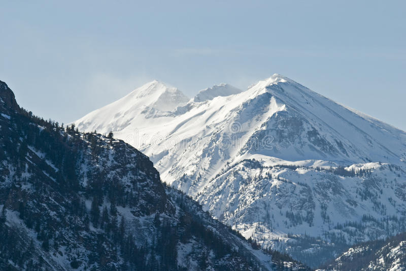 High mountain snowcaps. The high winds move the snow on the forbidding mountain into early autumn stock images