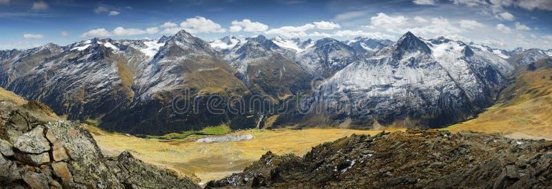 High mountaines meadow. Alpine mountaine meadow. Snowed tops stock photos