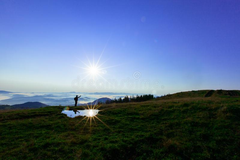 High in the mountains above the clouds a young man is looking for a cellular connection holding his phone high royalty free stock photos