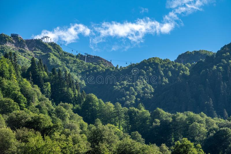 High mountains with green slopes and cable lifts. Clear blue sky in the summer mountains royalty free stock photo