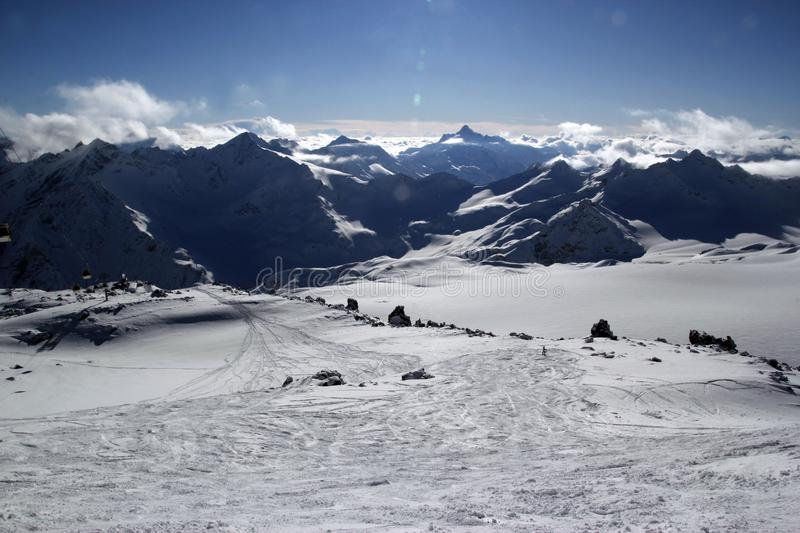High mountains off-piste slopes for freeride with traces of skis and snowboards, sunny winter day, Caucasus Mountains, Elbrus stock photo