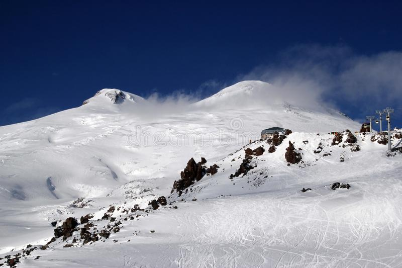 High mountains off-piste slopes for freeride with traces of skis and snowboards, sunny winter day, Caucasus Mountains, Elbrus royalty free stock image