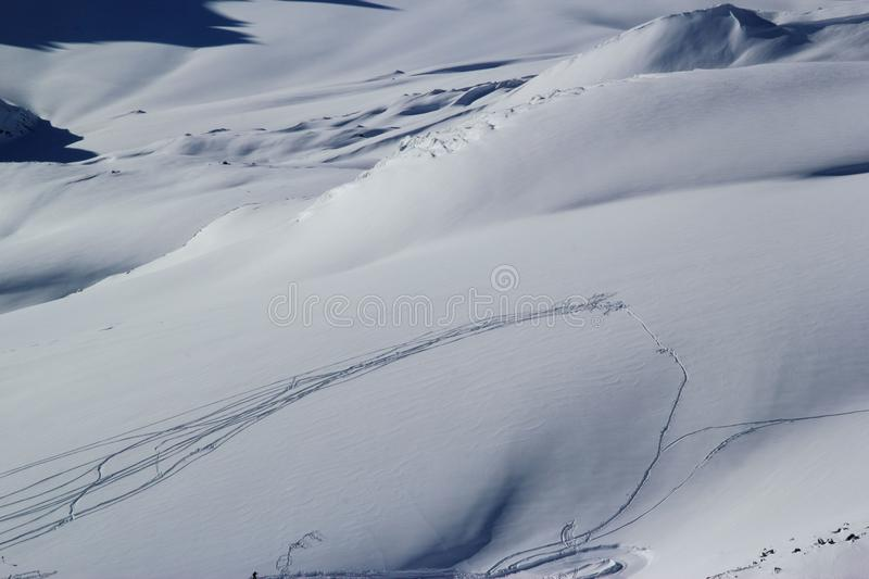 High mountains off-piste slopes for freeride with traces of skis and snowboards, sunny winter day, Caucasus Mountains, Elbrus royalty free stock photography