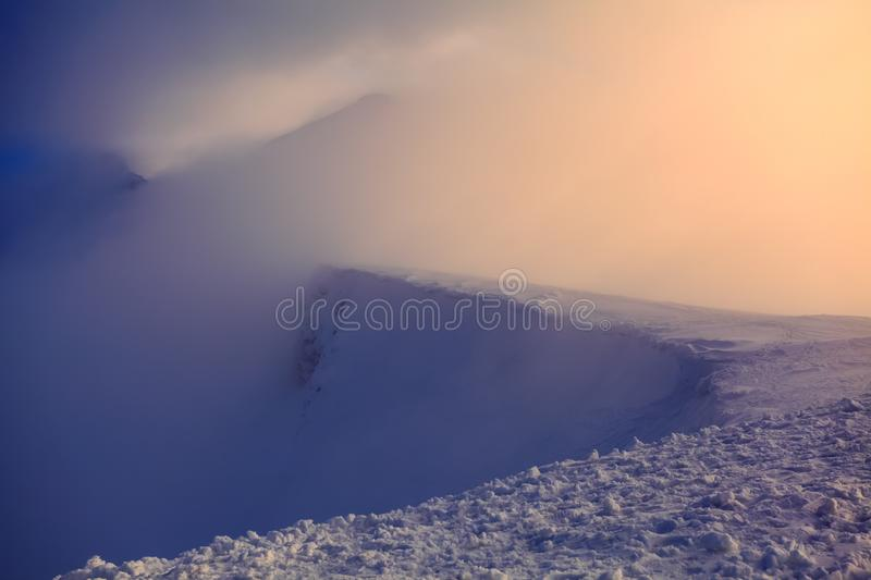 High in the mountains the sun is rising and enlightens everything with wonderful color. The mountains are in snow. stock images