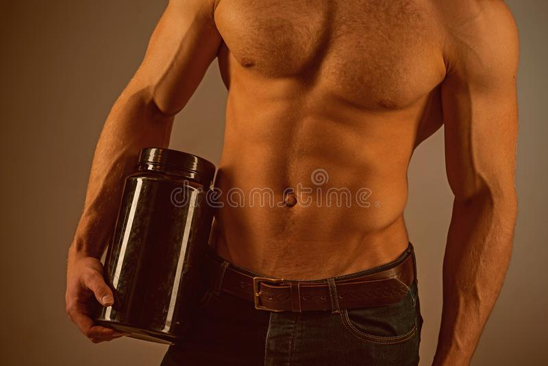 A high nutrient diet. Anabolic hormone increases muscle strength. Vitamin nutrition. Healthy diet. Strong man hold. Vitamin bottles. Man with six pack stock images