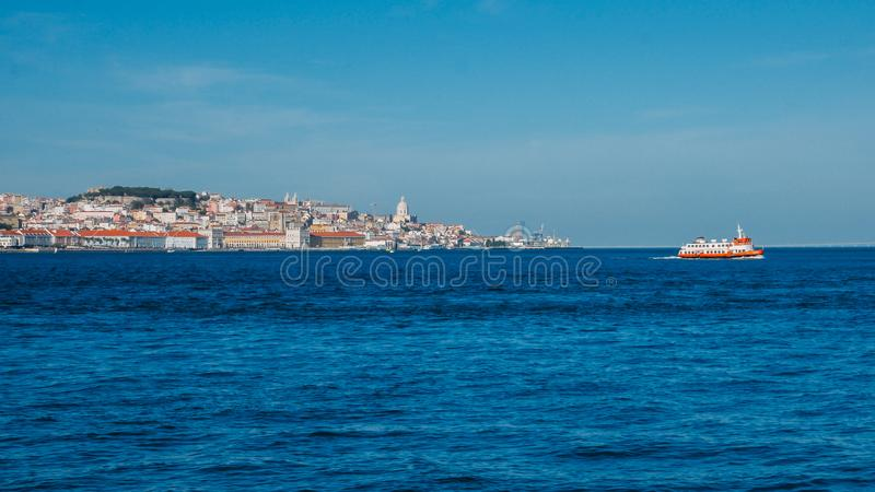 High perspective panorama of Lisbon old city center, view from Almada, Portugal with ferry boat crossing.  royalty free stock images