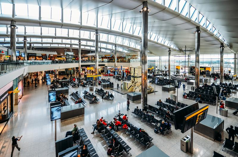 High perspective view of passengers and shops at departure terminal at Heathrow Terminal 3 in London, UK. London, England, Feb 13, 2019: High perspective view of stock photography