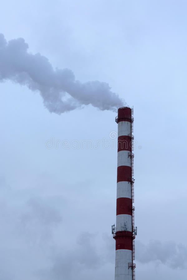 High pipe CHP on the background of blue sky, fog, smog. And out clouds of thick smoke, pipe red-and-white, it`s cold outside stock photo