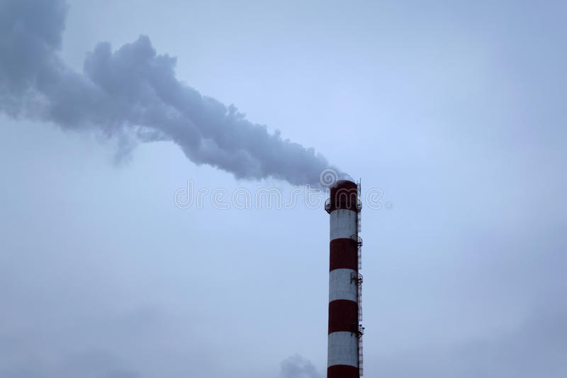 High pipe CHP on the background of blue sky, fog, smog. And out clouds of thick smoke, pipe red-and-white, it`s cold outside stock images