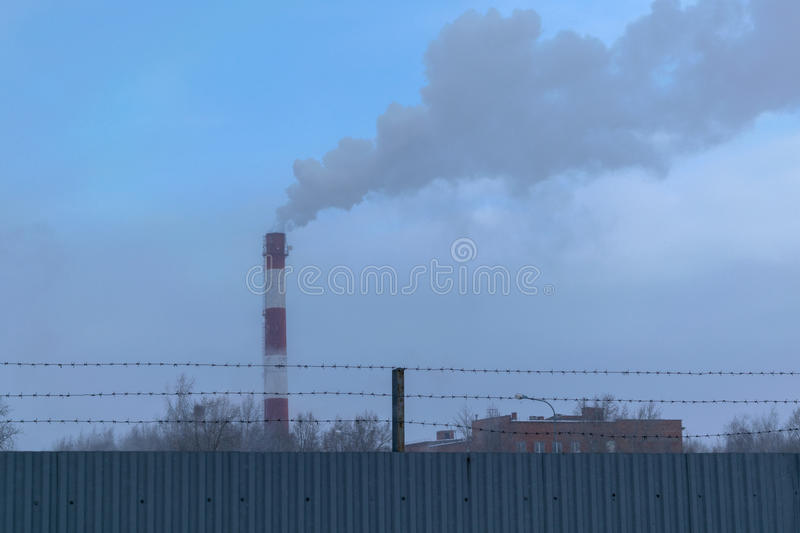 High pipe CHP on the background of blue sky, fog, smog. And out clouds of thick smoke, pipe red-and-white, it`s cold outside stock photography