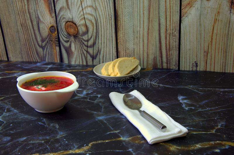 A high plate with real Russian red borsch, beside a napkin with a spoon and a saucer with slices of bread. Close-up royalty free stock photo