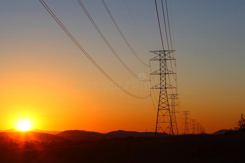 High-power electric distribution tower. A line of high-power electric distribution towers at sunset royalty free stock photo