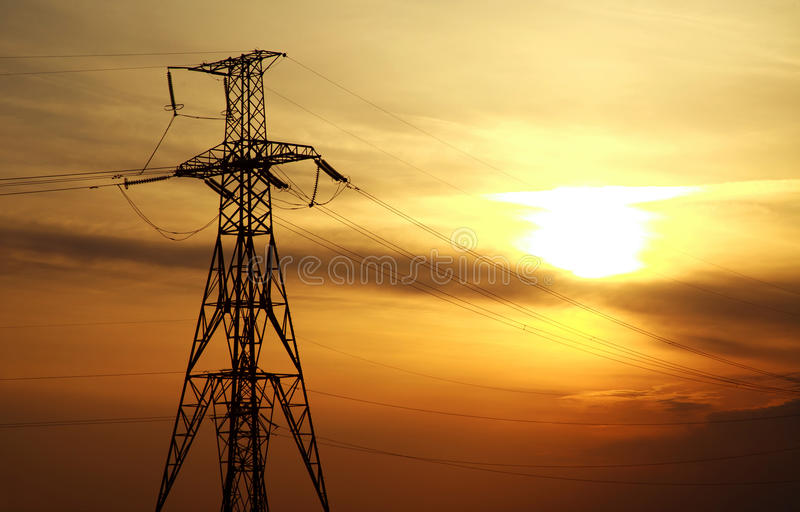 High power electric line towers at dramatic sunset. Background stock images