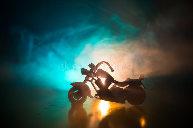 High power motorcycle chopper. Fog with backlights on background with man rider at night. Empty space stock photos