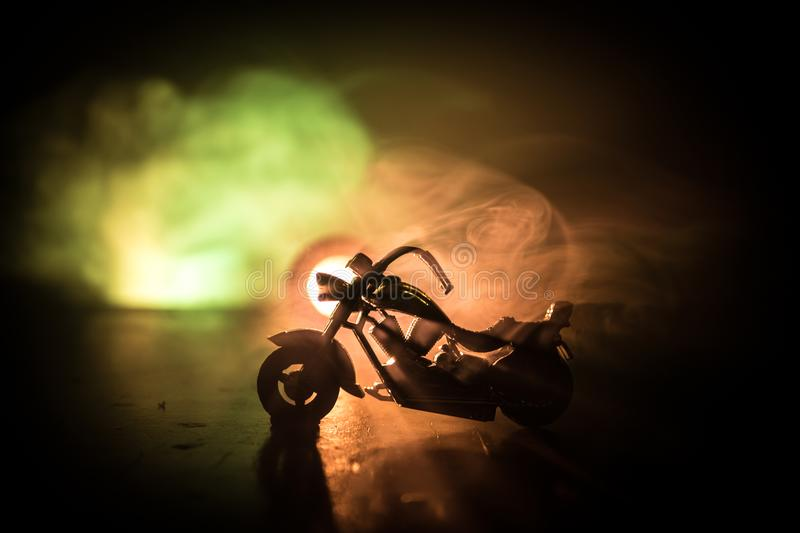 High power motorcycle chopper. Fog with backlights on background with man rider at night. Empty space royalty free stock image