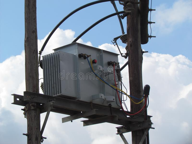 High power oil filled step down transformer on pole. A high power oil filled tep down transformer mounted on gum poles, used to supply 400V mains electricity royalty free stock photography