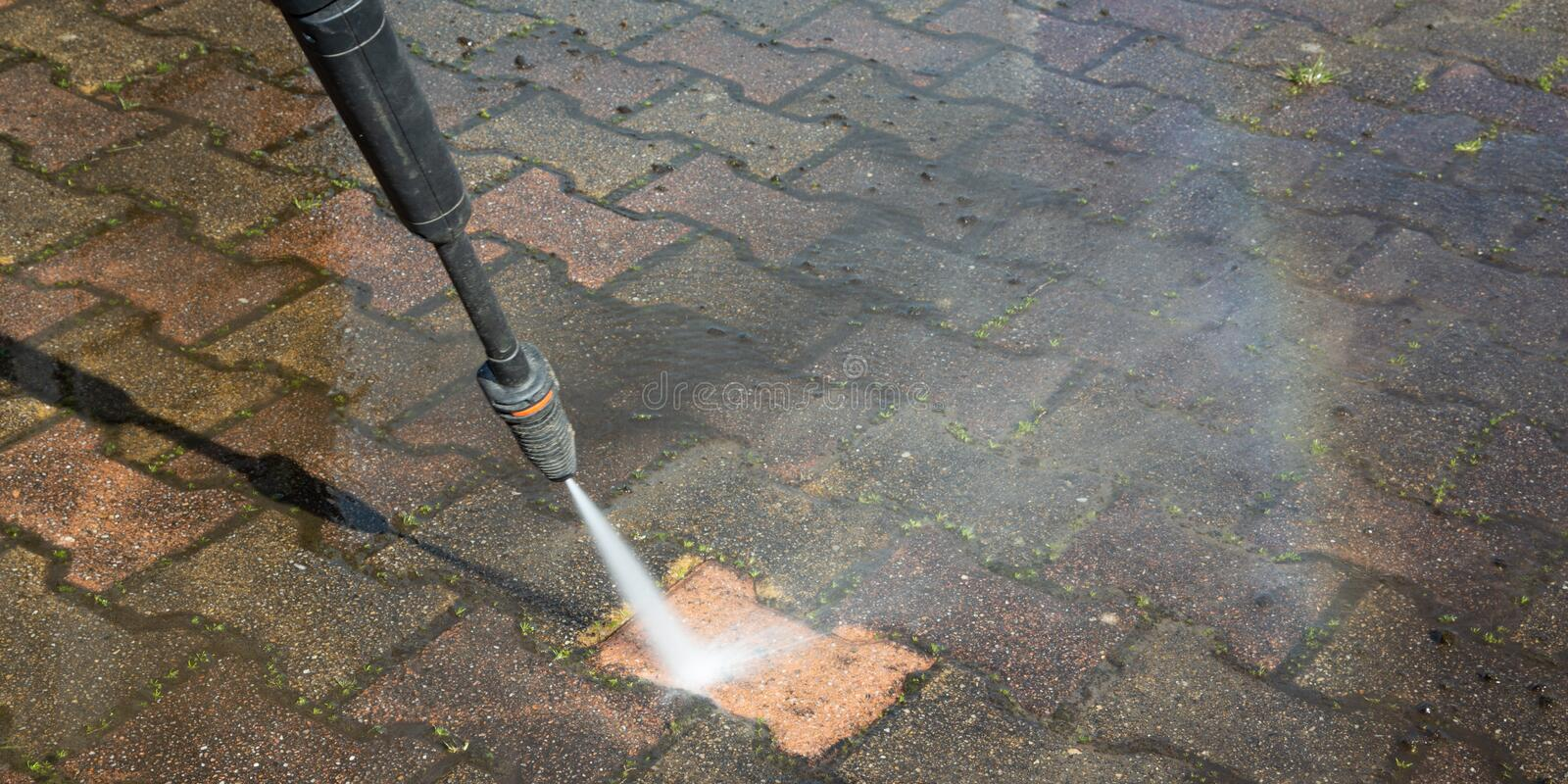 High Pressure Cleaning concrete block floor by water jet. A High Pressure Cleaning concrete block floor by water jet royalty free stock images